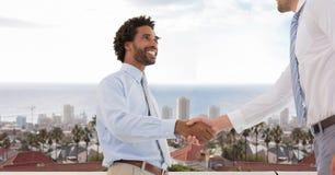 Businessmen doing handshake against city Royalty Free Stock Images