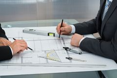 Businessmen drawing on the blueprints Stock Photography