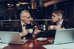 Businessmen drink coffee and look at each other royalty free stock image