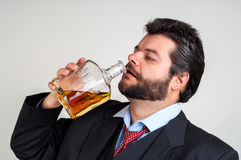 Businessmen drinking from a bottle of whiskey. Drunk businessmen drinking from a bottle of whiskey Royalty Free Stock Images
