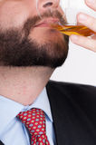 Businessmen drinking from a bottle of whiskey Stock Image
