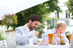 Businessmen eating food at outdoor restaurant Stock Image
