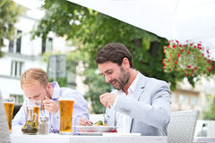 Businessmen eating food at outdoor restaurant stock photo