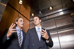 Businessmen in elevator conversing royalty free stock photos