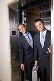 Businessmen in elevator looking out doorway Stock Photography