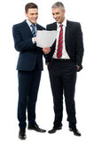 Businessmen evaluating deal documents. Smiling business executives checking documents Stock Photos