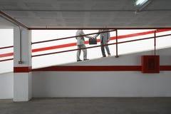 Businessmen Exchanging Briefcase On Ramp In Parking Garage Stock Photos