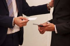Businessmen exchanging white blank name card, credit card or information on the smart phone. Conceptual Idea of information. Sharing, communication, connection Royalty Free Stock Photos