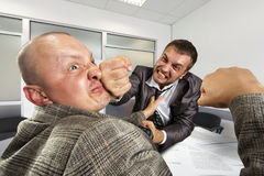 Businessmen fighting in the office royalty free stock photos