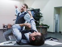 Businessmen fighting in the office Stock Photo