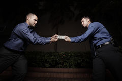 Businessmen fighting over money Royalty Free Stock Images