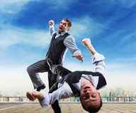 Businessmen fighting. Two businessmen fighting on the roof Stock Photography
