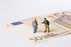 Businessmen figurines standing on euro banknotes stock image