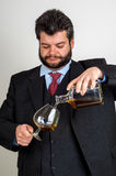 Businessmen filling a glass of whiskey. A businessmen filling a glass of whiskey Stock Images