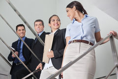 Businessmen flirting with women. Smiling businessmen flirting with two attractive women in the office stairway Royalty Free Stock Images