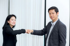 Businessmen giving fist bump after business achievement in meeting room. Stock Images