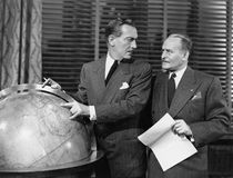 Businessmen with globe. (All persons depicted are no longer living and no estate exists. Supplier grants that there will be no model release issues Royalty Free Stock Image