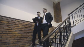 Businessmen go down the stairs and discuss project stock video footage