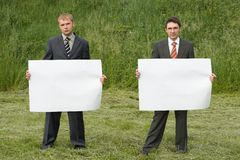 Businessmen on green grass background Stock Images