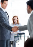 Businessmen greeting each other at a job interview. International businessmen greeting each other at a job interview in an office Royalty Free Stock Images