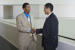 Businessmen Greeting Each Other In Office Hallway Stock Images