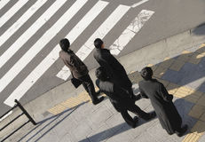 Businessmen group. Image of four businessmen group waiting to cross the street in a big (Asian) city Stock Images