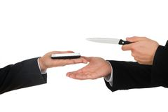 Businessmen hands with knife and mobile phone Royalty Free Stock Images