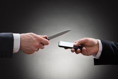 Businessmen hands with knife and mobile phone Royalty Free Stock Photos