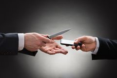 Businessmen hands with knife and mobile phone Stock Photography