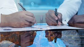Businessmen hands signing documents on Riyadh skyline city scape background stock photos