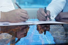 Businessmen hands signing documents on Riyadh skyline city scape background stock image