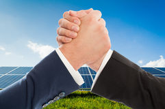 Businessmen handshake as teamwork on solarpower photovoltaic pan Royalty Free Stock Photos