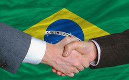 Businessmen handshake in front of brazil flag Royalty Free Stock Photo