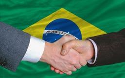 Businessmen handshake in front of brazil flag. Businessmen handshake after good deal in front of brazil flag Royalty Free Stock Photo