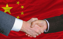 Businessmen handshake in front of china flag. Businessmen handshakeafter good deal in front of china flag Royalty Free Stock Image