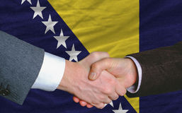 Businessmen handshake after good deal in front of bosnia herzego. Vina flag Stock Photos