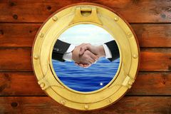 Businessmen handshake view from boat round window Royalty Free Stock Photo