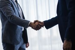Businessmen handshaking after good deal. Close up of two businessmen handshaking after good deal. Business people shaking hands and finishing up a meeting in stock photo
