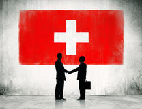 Businessmen Handshaking with Switzerland Flag Royalty Free Stock Photo