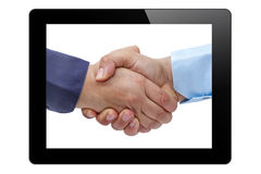 Businessmen handshaking tablet PC Stock Photography
