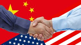 Businessmen handshaking on Usa or American and China flags merged relationship concept