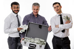 Businessmen have earned a lot of money. Young people with a suitcase full of money. Businessmen have earned a lot of money Royalty Free Stock Image