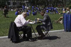 Businessmen have Lunch in the Park. New York, NY USA -- Aug 3, 2016  Two businessmen having lunch outdoors in Bryant Park on a sunny day. Editorial Use Only Royalty Free Stock Image