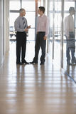 Businessmen Having A Discussion In Corridor. Full length of businessmen having a discussion in office corridor Stock Photos