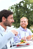 Businessmen having food at outdoor restaurant Royalty Free Stock Photo