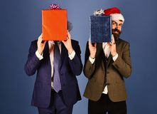 Businessmen hide faces behind red and blue present boxes. royalty free stock photos