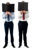 Businessmen hiding their faces with files Royalty Free Stock Images