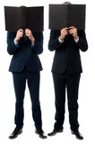 Businessmen hiding their faces with folder Royalty Free Stock Image