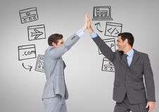 Businessmen high five with technology screens business graphics drawings Royalty Free Stock Photography