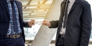 Businessmen hold jigsaw puzzles for each other. Business teamwork concept royalty free stock photography